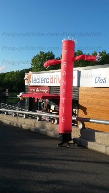 Un skydancer 1 jambe de 4m à l'effigie de la marque banette devant une boulangerie